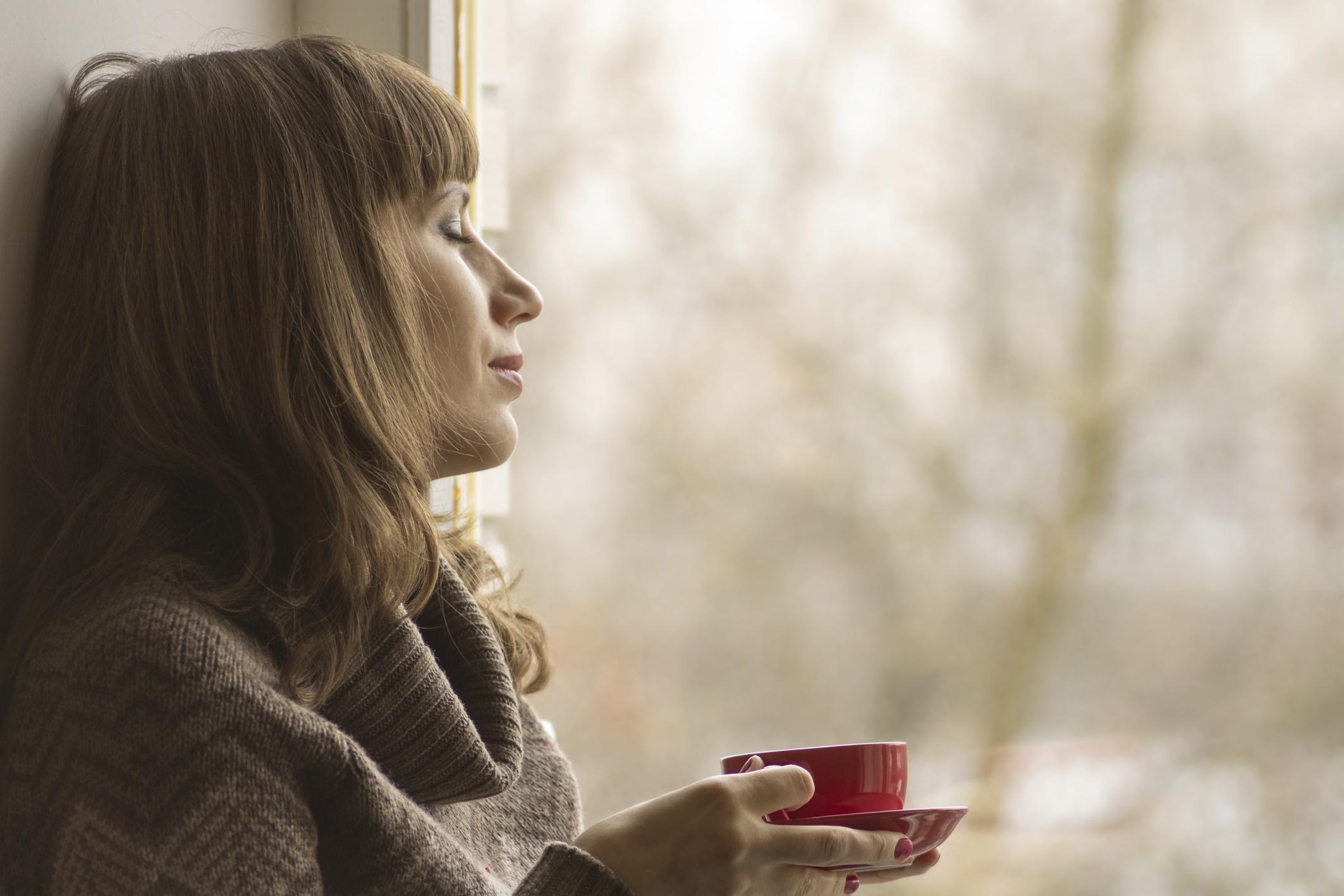 Фото девушка у окна с чашкой кофе