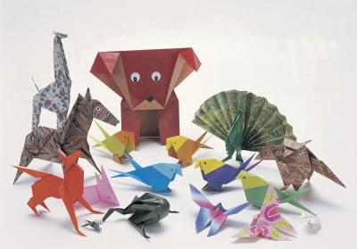 Many diferent origami animals sit on a Montroll base.